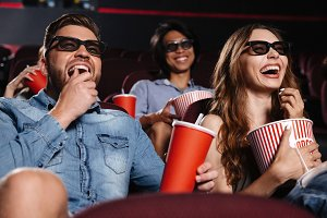 Laughing friends sitting in cinema watch film