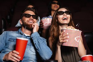 Happy friends sitting in cinema watch film