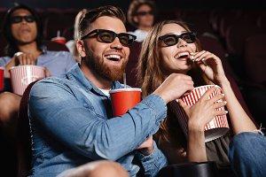 Happy friends sitting in cinema watch film eating popcorn