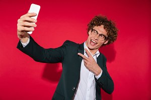 Happy man in eyewear taking selfie and showing peace gesture