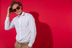 Smiling trendy young man in sunglasses and shirt posing