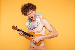 Attractive shirtless man in summer clothes playing ukulele