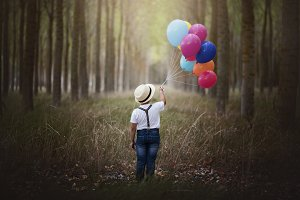 Child with balloons in the forest