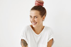 Profile of pleasant-looking lovely woman with dyed hair tied in knot, having tattooed arms, wearing white T-shirt, looking shyly at camera, smiling gently, receiving compliments from handsome guy