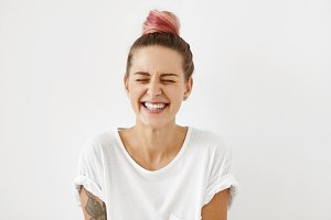 Gorgeous woman with pure healthy skin, pinkish hair knot and white perfect teeth closing her eyes with enjoyment being happy to find out that she is pregnant. Happy young woman laughing broadly