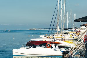 White sailing yachts in harbor at the pier in summer