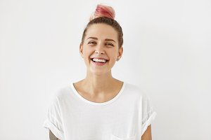 Indoor shot of beautiful positive female with pink hair bun, blue appealing eyes and healthy pure skin, smiling broadly demonstrating her white perfect teeth, isolated on white studio background