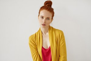Serious assured good-looking girl, having red hair bun, freckled skin, thin lips and green eyes, wearing red shirt and yellow cape posing in studio against white background. Confidence and assuarance
