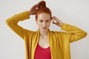 Confident female with red hair bun, freckled healthy skin and green eyes, keeping her hands on head, posing against white background in red T-shirt and yellow loose cape. People, fashion, beauty