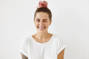 Stylish female with pinkish hair bun, blinking her eyes, smiling broadly, having joy indoors. Beautiful positve woman in white T-shirt expressing positive emotions and feelings. Happiness concept