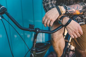 Unrecognizable young man sits on a bicycle, his hands on the steering wheel near the colorful blue wall