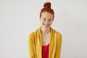 Portrait of young female model closing her eyes and smiling broadly while feeling joy. Red-haired girl with freckled skin, wearing colorful clothes, having pleasant dreams while resting at home