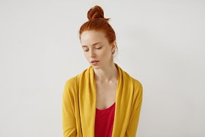 Calm woman with freckled skin, bright ginger hair, wearing red T-shirt and yellow cape, looking down with dreamy expression, thinking over her life. Dreamy red-haired woman isolated over white wall