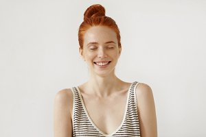Redhead pretty girl with freckled skin, closing her eyes with happy expression, smiling broadly, anticipating to recieve present from her boyfriend. Ginger young woman waiting for pleasant surprise
