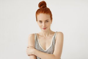 Studio shot of attractive woman with reddish hair knot and freckled skin, wearing striped loose T-shirt, keeping hands crossed, looking confidenlty. Beautiful young female relaxing at home alone