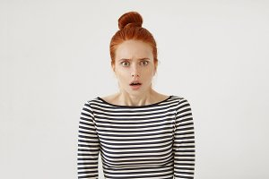 Grumpy female with red hair knot looking angrily into camera with slightly opened mouth, curving her eyebrows being dissatisfied with something. Discontent red-haired woman posing in white studio
