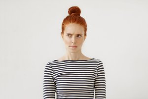 Pensive redhead woman with hair bun, curving her lips and raising eyebrows while thinking over or making important decision, having hesitations and doubled feelings. Thoughtful freckled female