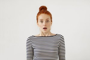Worried young red-haired woman dressed casually, looking with bated breath not expecting to see someone or something. Puzzled female with reddish hair isolated over white background. Confusment
