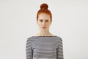 Serious displeased female with freckled skin, green eyes and red hair, wearing striped sweater looking directly into camera, isolated over white background. Ginger young female resting at home