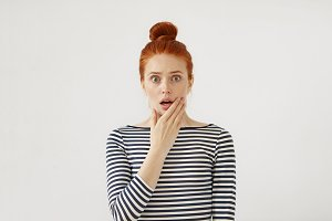 Female model with freckled face, reddish hair bun and green eyes, keeping her hand under chin, looking with surprised expression, being shocked with unexpected astonishing news. Facial expressions