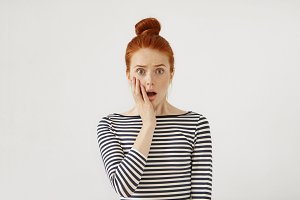 People, suddenness and surprise concept. Surprised female with red hair tied in bun, wearing striped sweater, keeping her hand on cheek, opening mouth. Redhead young girl with puzzled expression