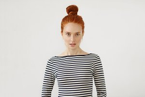 Cute girl with pleasant features, ginger hair tied in knot, dressed casually, looking with slightly parted lips in camera, having confident expression. Charming female with red hair and freckles