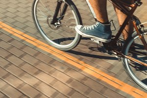Unrecognizable Cyclist In Sneakers Rides A Bicycle Path Motion Blur. Point Of View Shot