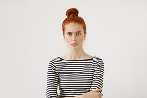 Serious female model with reddish hair tied in bun, standing against white background in casual sweater, keeping her hands crossed, looking with widely opened eyes and suddenness into camera