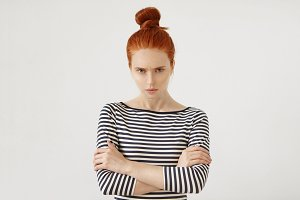 Angry ginger female with hair knot, wearing casual clothes, keeping her hands crossed, looking with displeased expression into camera, having quarrel with her boyfriend or parents. Negative emotions