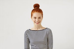 Beautiful red-haired female with bun, freckled face and green appealing eyes, smiling gently into camera while having good mood after party with friends. People, fashion, lifestyle, emotions concept