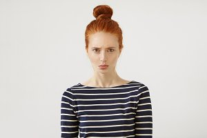 Discontent redhead teenage girl wearing casual striped sweater, having gloomy expression after failing her exam. Ginger female with hair knot and freckles posing against white wall with copy space