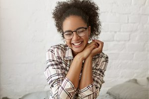 Stylish teenage girl wearing hipster eyeglasses and plaid shirt laughing, enjoying free time indoors, sitting on sofa against white brick wall background. Happiness, fun, joy, leisure and relaxation
