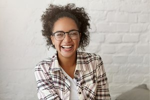 Beautiful emotional young mixed-race female in good mood relaxing at coffee shop laughing at joke or funny story. Pretty girl wearing glasses and checkered shirt smiling broadly, resting at cafe