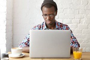 Stylish young dark-skinned male translator in eyewear and hat sitting in front of generic laptop, having serious focused look while working remotely, translating scripts for series at coworking space