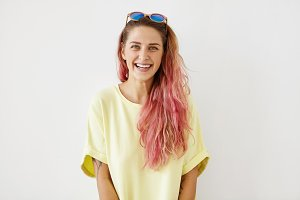 Beautiful young woman with pink long hair, appealing blue eyes and healthy skin, wearing yellow casual T-shirt and stylish sunglasses on head, smiling gently while posing against white background