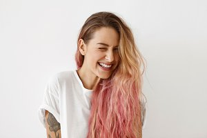 Young female model with pink hair tips, winking her eyes while having joy, smiling broadly, feeling joy. Beautiful hipster female with long hair feeling happiness while being photographed in studio