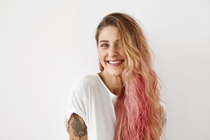 Lovely female with pure skin, blue shining eyes and pink hair tips, wearing casual T-shirt, smiling pleasantly into camera while having good mood in morning. Stylish hipster woman with tatooes