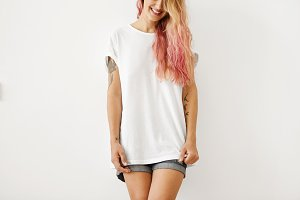 Young slim woman with long hair colored in pink, having tattooed arms, wearing white T-shirt with copy space for your print or advertisment, posing against white background. People, style, fashion