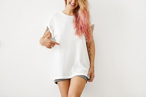 Slim woman with pink hair tips, wearing white loose T-shirt and jean shorts, pointing at copy space for your text message or promotional content, isolated over white studio background. Clothes, design