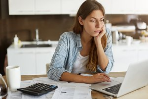 People, accounting, finances, family budget and financial issues concept. Serious young European woman calculating domestic expenses, sitting at dining table in front of open laptop computer