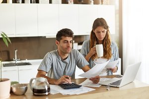Frustrated young man and woman in casual clothes managing finances together: female with coffee studying sheet of paper in her hands while her husband calculating domestic bills using calculator