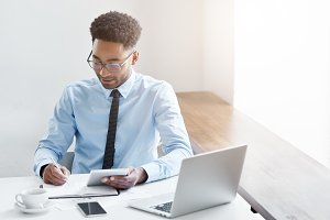 Successful young male dark-skinned accountant with Afro hairstyle and bristle using digital tablet, making notes in copybook, analyzing financial data, sitting at desk surrounded with modern gadgets