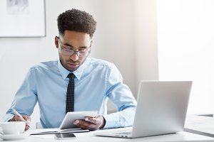 Ordinary morning in office. Candid shot of serious young black European employee in spectacles working in office holding generic digital tablet and making notes, looking focused and concentrarted
