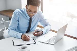 Concentrated young Afro-American financial analyst in glasses holding mobile phone and writing down information in copybook, working on report or presentation at his light and spacious workspace