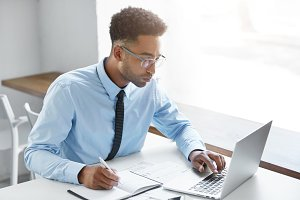 Handsome young dark-skinned manager with stubble wearing eyeglasses and blue shirt with tie having concentrated look while working on presentation using laptop computer, writing down in notebook