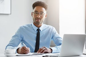 People, business, work, job, occupation and profession concept. Attractive positive hardworking young Afro-American office worker sitting at desk in front of open laptop pc and making notes