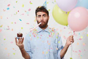 Studio shot of surprised shocked young unshaven man looking at camera in astonishment, holding balloons and birthday cake, taken by surprise by colleagues in office who prepared party for him