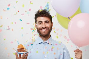 Portrait of cheerful good-looking birthday guy with beard standing at white wall, holding colorful balloons and birthday cupcake, smiling broadly, happy with surprise party that friends made for him