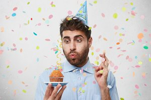Attractive man who is celebrating his birthday, blowing out candle on cupcake, crossing his fingers while making wish. Bearded male in party cap and shirt holding tasty cake, having some dreams