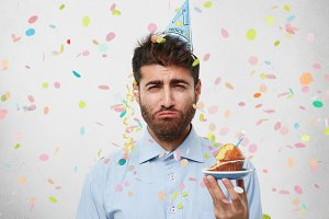 Headshot of sad disappointed man wearing cone hat on his hand, posing at studio wall with confetti falling down, having unhappy look as he hates celebrating birthday, holding cupcake, going to cry